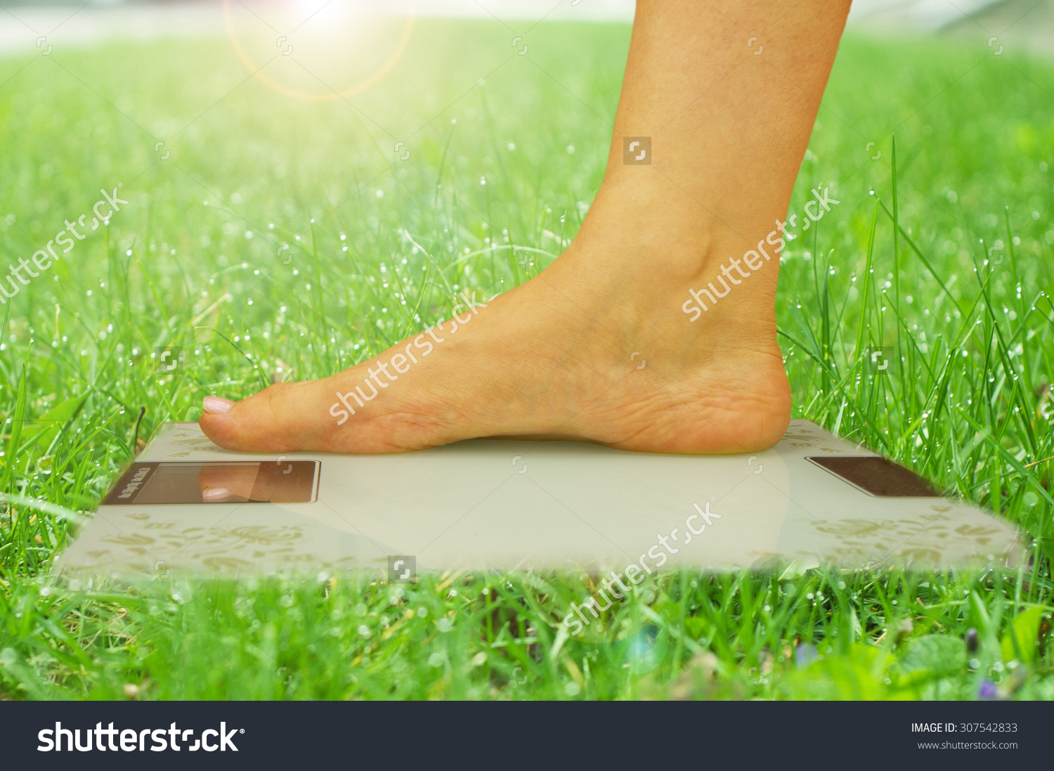 stock-photo-foot-on-the-scale-on-grass-background-nature-307542833