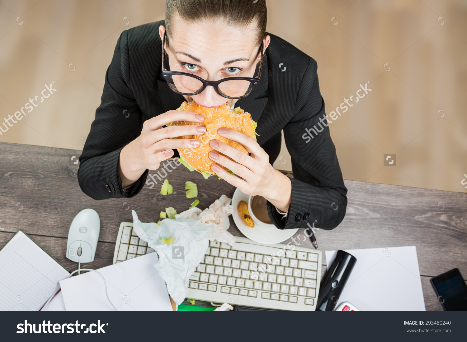 stock-photo-overhead-view-of-businesswoman-eating-at-computer-in-office-at-work-place-the-modern-pace-of-life-293480240